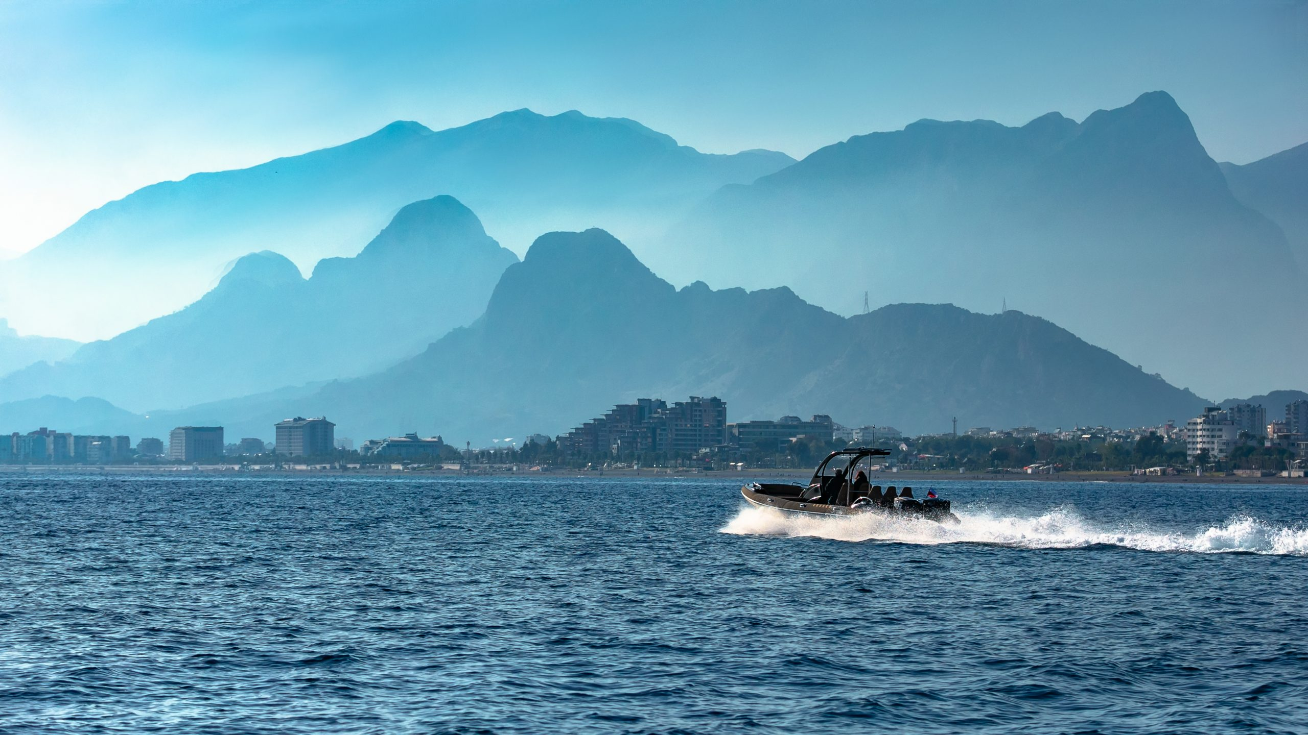 RHIBs on water in front of mountains